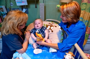 Brantley Strunk is cared for by Respiratory Therapist Amie Keck, left, with help from his grandmother, Becky Lamson, right.